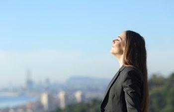 A businesswoman breathing fresh air through her nose.